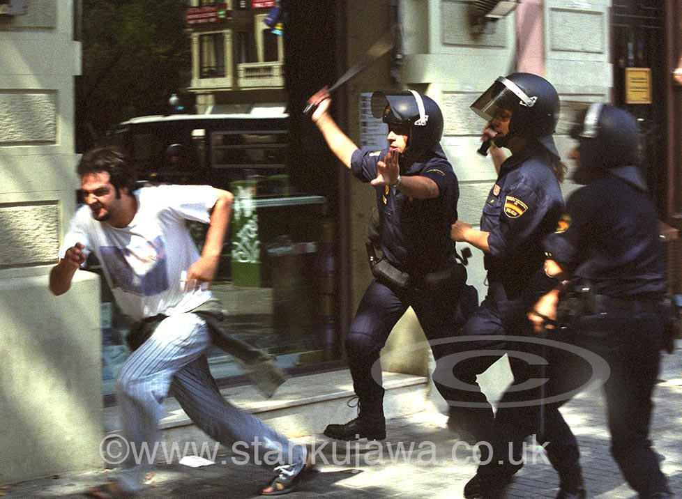 Spanish Riot police officers hit an anti-capitalist protestor with baton in Barcelona during anti-World Bank demonstrations.  24.06.01. Barcelona, Spain. ©Stan Kujawa 1998-2013. All Rights Reserved. Image may not be used without the express written permission of the author.
